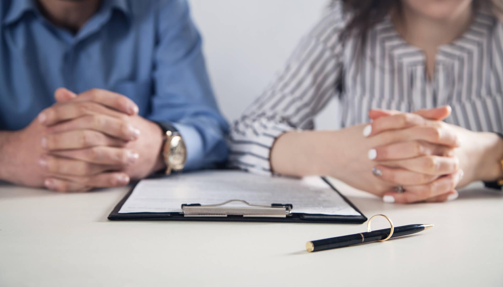 Mann und Frau bei der Unterschrift des Ehevertrags